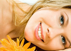blond-haired woman laying on her side and smiling with a flower in the foreground