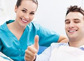 dentist in blue scrubs sitting next to man giving a thumbs-up