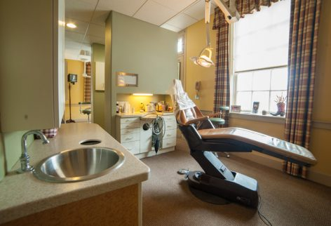 an examination room with yellow walls and a dental chair