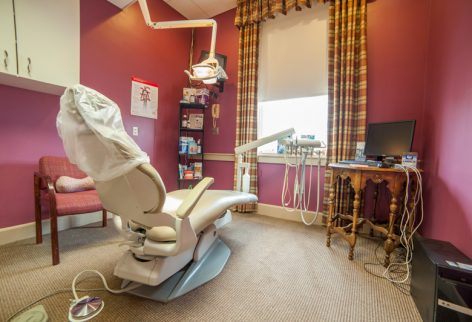 a dental examination room with red walls and a dental chair